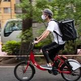 写真:自転車を2人乗りして配達するカップル